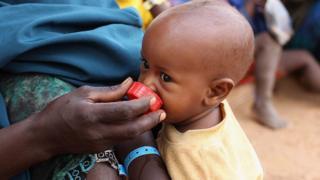 Un enfant réfugié somalien boit de l'eau à partir d'un bouchon de bouteille dans la zone d'enregistrement du camp de réfugiés IFO qui fait partie de l'immense camp de réfugiés de Dadaab le 23 juillet 2011 à Dadaab, au Kenya.