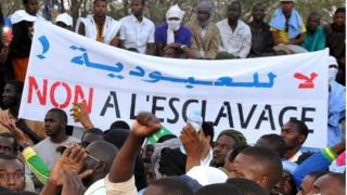 People hold a banner reading 'No to slavery' during a demonstration against discrimination in Nouakchott on April 29, 2015.