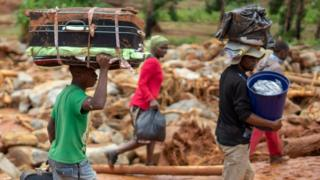Cyclone survivors leave the Ngangu township with their belongings to Chimanimani Hotel in Zimbabwe - 18 March 2019