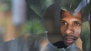 Warga melihat di balik kaca jendela yang pecah di Jayapura