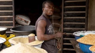 Un Nigérian pose à côté d'un peu de riz dans son magasin au marché Ajara à Badagry, près de Lagos, le 6 septembre 2019.