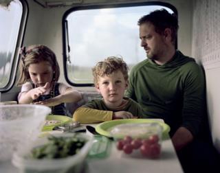 A family sit in their caravan.