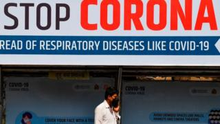 "An Indian man wearing a face mask walks past a giant sign reading ""stop Coronavirus"""
