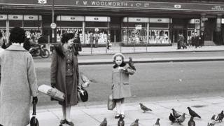 Girl poses with a pigeon on her elbow