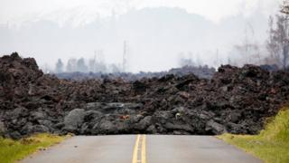 A lava flow covers a road in the Leilani Estates subdivision during ongoing eruptions of the Kilauea Volcano in Hawaii, U.S., May 13, 2018.
