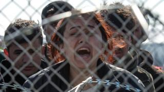 Woman shouts and cries on the Greek side of the border with Macedonia