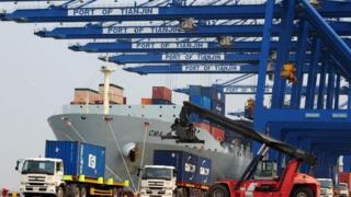 Shipping containers being loaded onto trucks from a cargo ship at Tianjin port in China