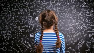 Girl looking at maths sums on a blackboard