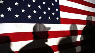 Workers silhouetted against the US flag