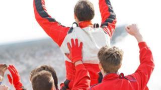 Un corredor de Fórmula 1 victorioso, saludando a los espectadores