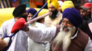 A man performing Gatka - the Sikh martial art - as part of a procession in Amritsar