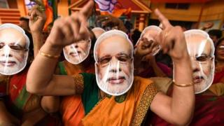 """Indian Bharatiya Janata Party (BJP) supporters wearing masks of Indian Prime Minister Narendra Modi dance as they celebrate on the vote results day for India""""s general election at BJP office in Guwahati on May 23, 2019"""