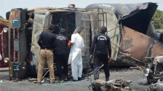 La policía revisa el camión de combustible que explotó y se quemó el 25 de junio en Punyab, Pakistán.