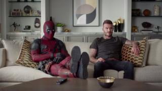 Deadpool and David Beckham watching TV