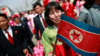 A North Korean woman carries the national flag after a parade for the 'Day of the Sun' festival