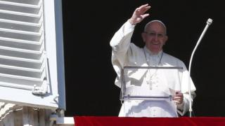 Pope Francis waves as he leads his Angelus prayer in Saint Pater's square at the Vatican