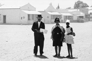 An elder of the Dutch Reformed Church walking home with his family after the Sunday service, Carnavon, Cape Province (Northern Cape), January 1968.