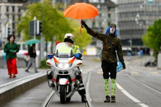 A protester dressed as a clown holds an umbrella over a Swiss police officer on a motorbike during a May Day demonstration in Zurich, Switzerland