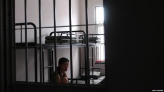 A woman inmate looks out of a ward at a detention centre 24 June 2005