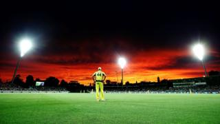 Australian cricketer James Faulkner stands in the field beneath the brilliant sky.