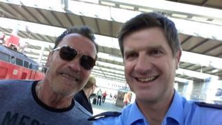Arnold Schwarzenegger takes a selfie with officer Stefan Schmidt
