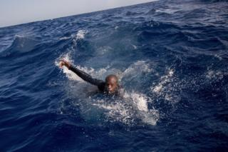 A migrant tries to board a boat of the German NGO Sea-Watch in the Mediterranean Sea on November 29, 2017. During a shipwreck, five people died, including a newborn child. According to the German NGO Sea-Watch, which has saved 58 migrants, the violent behavior of the Libyan coast guard caused the death of five persons.