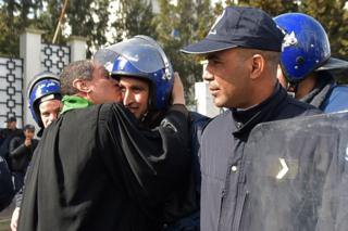 An Algerian lawyer kisses a policeman during a protest against ailing president's bid for a fifth term in power, in Algiers on 7 March 2019.