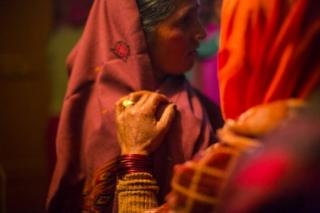 Celebration of a traditional indian marriage with bride, indian woman wearing festive clothes and groom, mother in law and father in law, friends and family on December 01, 2012
