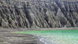 The cliffs of the crater lake are etched with erosion gullies