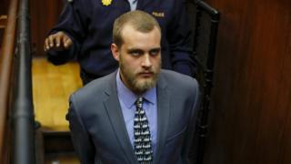 Henri van Breda being led away after being sentenced to three life terms by a judge