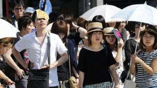 People wait to cross the road as they use umbrellas and hats to shade themselves from the sun in Tokyo