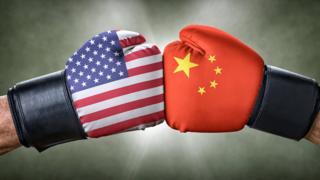 Dos puños enfrentados con las banderas de EE.UU. y China.