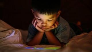 Anak melihat layar tablet.