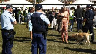A festival goer is approached by a police sniffer dog and several police at a music festival in Sydney