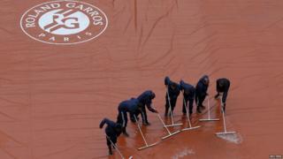 Rain being swept off tennis court