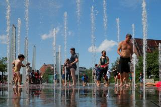 Kids and adults cool off in a fountain on the Rose Kennedy Greenway on the first day of a forecasted summer heatwave in Boston, Massachusetts