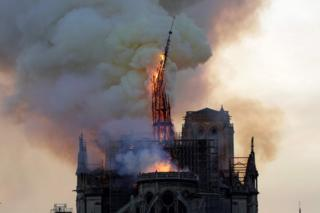 The spire of the landmark Notre-Dame Cathedral collapses as the cathedral is engulfed in flames in Paris on 15 April 2019.