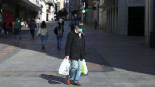 Man with bags in empty Madrid street