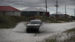 A car drives on a flooded road in Dauphin Island, Alabama