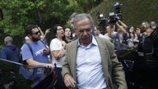 Paulo Guedes caminha em rua cercado por jornalistas