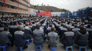 Prisoners sitting in rows in a prison yard for an event