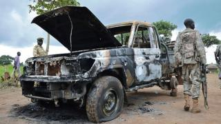 South Sudanese SPLA soldiers inspect a burned out car in Pageri in Eastern Equatoria state on August 20, 2015