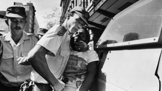 South African police officers aggressively arrest Moses Mayekiso, a prominent trade union leader, during a protest march in Johannesburg, South Africa (archive shot)