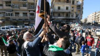 Syrian activists hoist an opposition flag during a protest in Aleppo (7 March 2016)