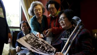 South Korean participants for a reunion check old pictures at a hotel used as a waiting place in Sokcho, South Korea (19 October 2015)