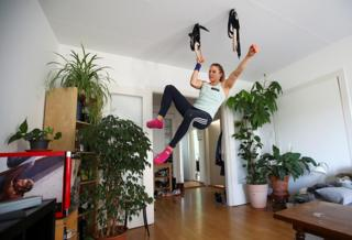 A climber dangles from handles in the ceiling of her living room