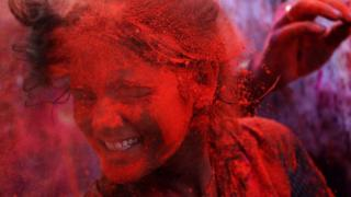 A girl is covered in red paint powder