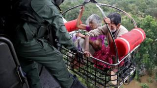 Two elderly people being airlifted away from floods