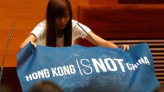 Newly elected lawmaker Yau Wai-ching displays a banner before taking oath at the Legislative Council in Hong Kong, China October 12, 2016.