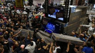 """يتهافت المتسوقون على المتاجر في """"الجمعة السوداء"""" ويتزاحمون للظفر بأفضل العروض."""